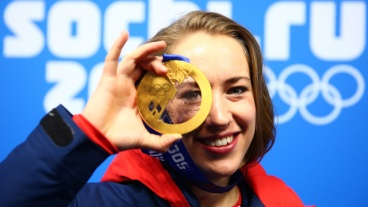 Lizzy Yarnold holds up her gold medal